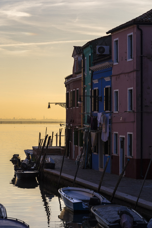 Waterfront canal on the island of Burano, houses and boats parked on the background of beautiful sunset. Italy