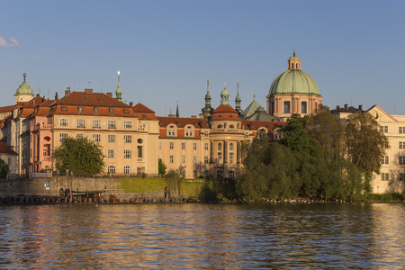 st charles: Vltava embankment with a church and hospital of St. Francis of Assisi in the vicinity of the Charles Bridge in Prague. Czech Republic Stock Photo