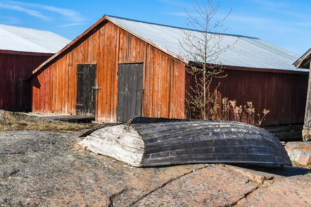 sheds: Old broken boat on the wooden sheds for storage of boats in the background. Aland Islands
