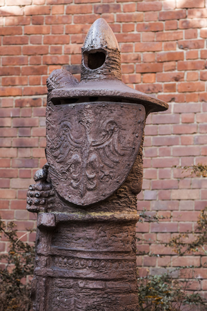 Metal idol in the old city wall. Warsaw. Poland