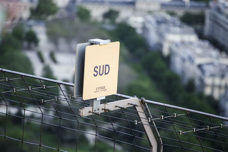 A sign on the fence with an indication of the direction of the floor and sides of the world Stock Photo