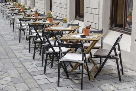 Tables and chairs in a row along the wall there are cafes in the street Stock Photo