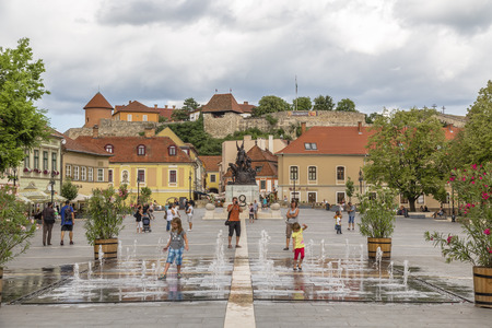 EGER. HUNGARY - JULY 18, 2016: Istvan Dobo Square with a fountain in the foreground and the castle in Eger in the background. Hungary Editorial