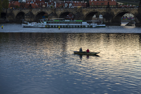 Fishermen in small boat fishing near the Charles Bridge in Prague on a background of pleasure craft at sunset. Prague. Czech Republic Editorial