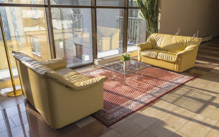 Hall building with two leather couches and glass table in bright sunlight