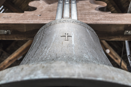 The big church bell with a cross on the body