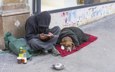 PARIS, FRANCIA - 17 de mayo, 2016: clochard con el perro sentado junto a la pared del edificio en la calle de París. Francia. Editorial