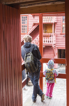second floor: Two people standing with his back to the camera on the balcony of the wooden house