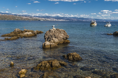 croatian: Rocky sea shore and boulders sticking out of the water. Opatija. Croatia