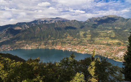 Lake Iseo with settlements on the shore and a mountain range around. Lombardy. Italy