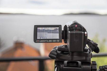 tripod mounted: A video camera mounted on a tripod shoots a landscape with a yacht Stock Photo