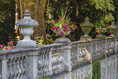 Large garden vases with flowers on stone fence
