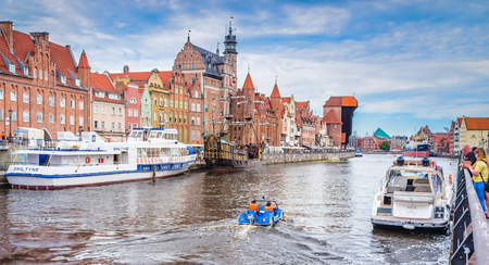 GDANSK, POLAND - AUGUST 02, 2017: Facades of buildings on the embankment of the river with pleasure boats and yachts, an excursion pirate ship and the construction of the XV century - Zhurav, combining several functions - the city gate, defensive tower an Editorial