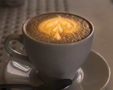 A cup of cappuccino with a beautiful foam and a pattern of cinnamon