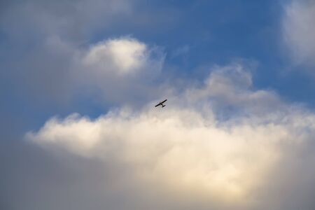 A small, sporty, lightweight screw aircraft in the space between the clouds against the blue sky