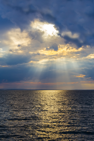 The rays of the setting sun make their way through dense clouds over the Baltic Sea