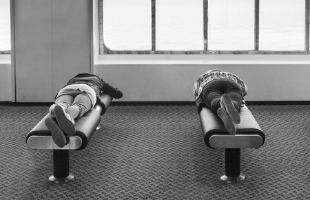 Two tourists rest on soft benches in the public zone, traveling on board a large ocean ferry without paying a stay in the cabin.