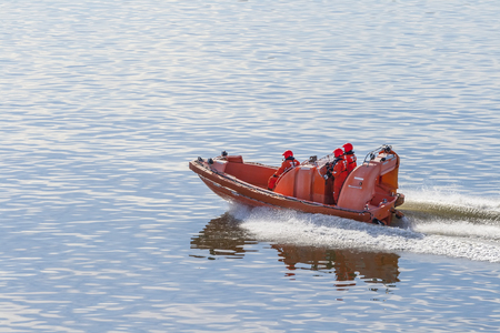 Rescue team in orange uniform on a motor boat at high speed patrols the water area Stock Photo