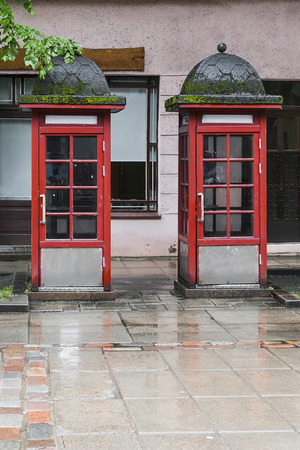 Two telephone booths of red shades stand side by side on the street in rainy weather against the backdrop of a pink building with windows.