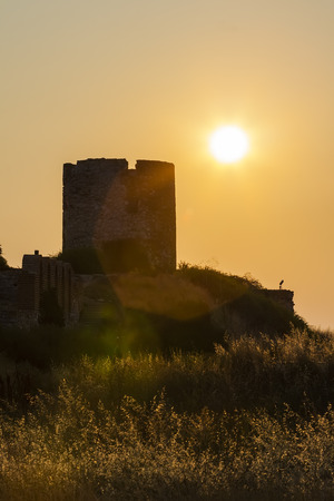 Remains of an ancient white stone mill on a hilltop in the backlight of the sun. Nessebar. Bulgaria Stock Photo