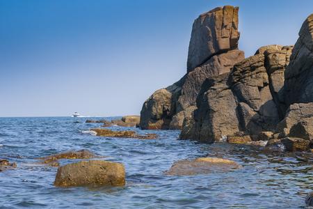 Rocky seashore against the blue sky and motor boat on the horizon. Nessebar. Bulgaria Stock Photo