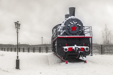 A large black steam locomotive with a red proletarian star stands on the canned section of the railway Stock Photo