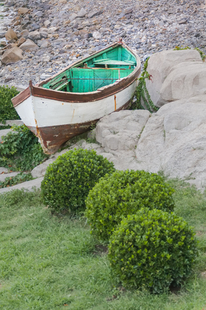 A wooden boat lies on the seashore among large stones and green bushes