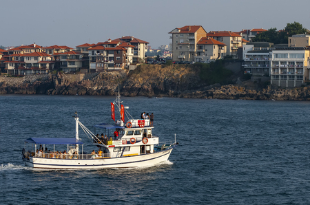 SOZOPOL, BULGARIA - JULY 27, 2011: A promenade yacht skates tourists on the Black Sea against the backdrop of modern private houses and fashionable hotels located on a high steep bank Editorial