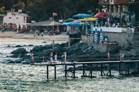 SOZOPOL, BULGARIA - JULY 27, 2011: Vacationers are photographed against the backdrop of the sea on a far-reaching pier in the resort town at sunset Editorial