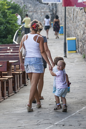 SOZOPOL, BULGARIA - JULY 27, 2011: Young pretty women are walking along a narrow street along the sea in a resort town holding the hand of young children at sunset