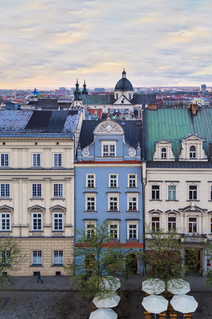 Houses on the market square and the Church of St. Anne on the background of the setting sun in Krakow. Poland Stock Photo
