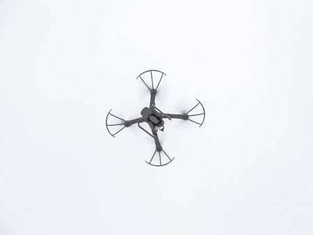 Quadrocopter in flight against a cloudy sky background Stock Photo