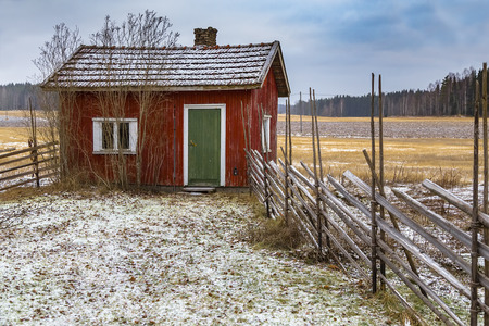 A small house on the background of a snow-covered field and a forest Stock Photo