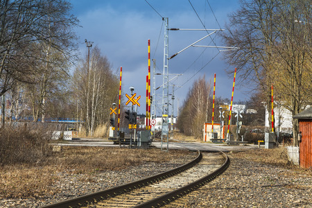 Automatic railway crossing with a barrier on a bright, sunny, spring day in the city of Turku