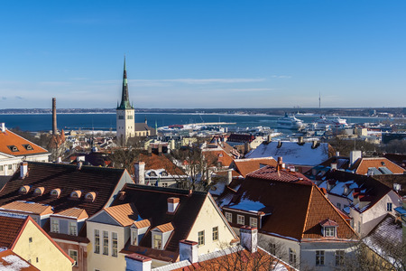 The roofs of the houses of old Tallinn, the Church of St. Olaf and the Tallinn Bay of the Baltic Sea with large sea ferries. Tallinn. Estonia