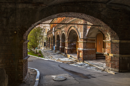 Arched passage to the courtyard of the old church and the old brick colonnade in Moscow