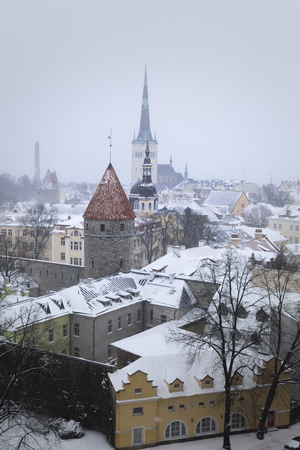 Estonia, Tallinn - a snow-covered city, an old fortress wall with towers, St. Olafs Cathedral