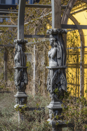 Carved wooden decorations on the stands of the greenhouse in the park surrounded by plants