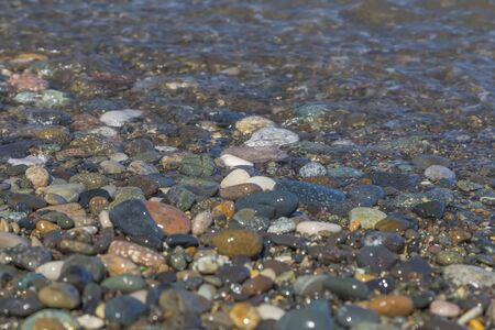 Motley pebbles turned to a semicircular state by sea surf