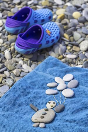 Beach still life with baby slippers and a funny little man with balloons laid out of pebbles on a blue beach towel Stock Photo