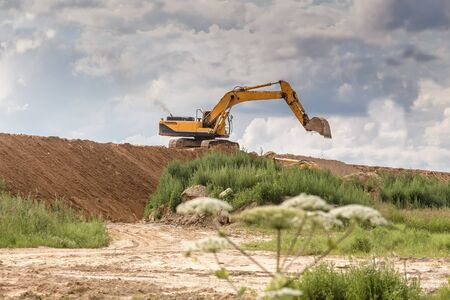 Excavator working on the construction of a sand mound in the field