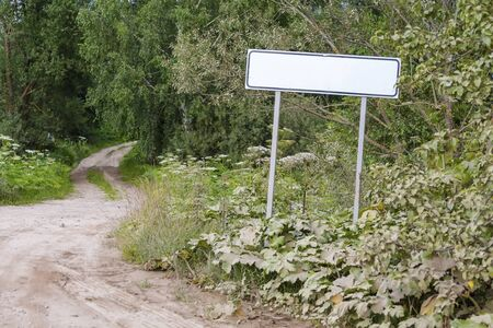 A sign on the road, indicating the beginning of the settlement, and a dirt road leading to the village
