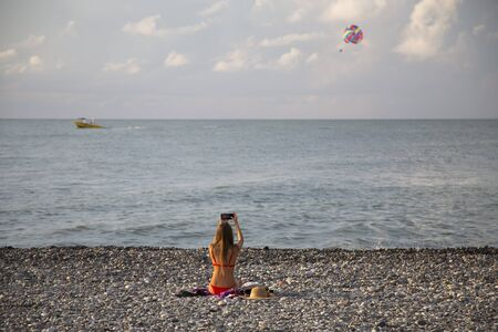 Batumi Georgia Girl in red bikini takes pictures of parasailing