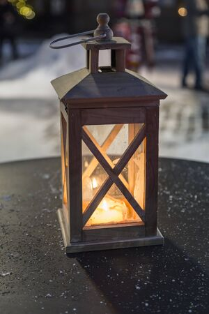 A wooden lantern radiates a cozy and warm light from the candles inside and illuminates the black surface of the metal table with frozen drops of water
