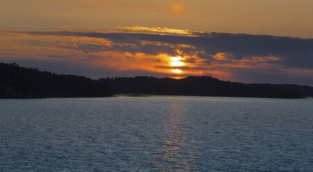 Turku, Finland - Sunset landscape, the light of the setting sun shines through the clouds and is reflected in the sea