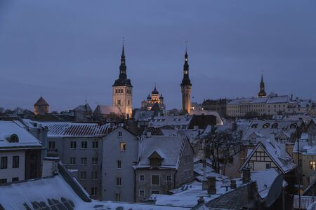 Tallinn, Estonia - Cityscape with a view of the evening city with domes and towers of churches with night illumination, fortress towers and residential old houses Stock Photo