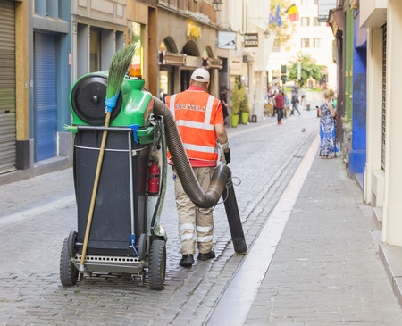 Brussels, Belgium - May 09, 2018: Vacuuming with a large vacuum cleaner on a city street. Editorial