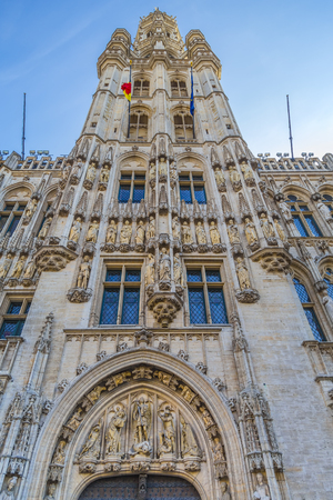 Brussels, Belgium - Tower of the Brussels Town Hall with lots of stucco and sculptures against a clear and cloudless blue sky at the sunset hour