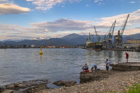 Batumi, Georgia - August 04, 2018: Batumi Sea Port with moored ships, port cranes and fishermen Editorial