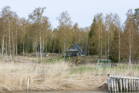 Spring landscape with a view of the forest and a small house on the lake